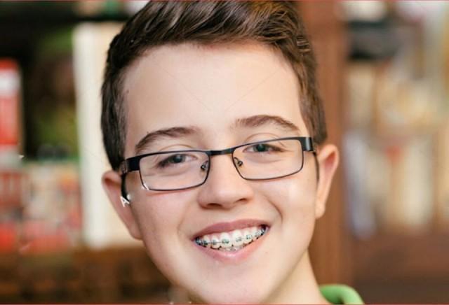 Chłopiec z aparatem ortodontycznym do świątecznej reklamy tv